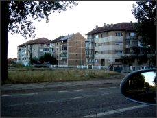 """Kvůli ní bylo vystavěno na břehu Dunaje město """"Moldova nova"""" vedle vesnice """"Moldova veche"""". Město, závislé na jedné fabrice, začalo chátrat asi hned po jeho dostavění. Přímý široký pobřežní bulvár je obklopený velkorysými socreal stavbami - sportovišti ozdobenými mozaikami se srpy a kladivy, hotely s oprýskanou fasádou, špinavými betonovými kostkami kulturních středisek. Všechny jsou prázdné. Rumuni se setkávají večer u cest, při shánění dobytka z pastvin a dlouho do tmy rokují a probírají události. To tady není. Zdejší lidi, kromě nezaměstnanosti, nemají o čem mluvit. Obytné domy, většinou paneláky, jsou strašně špinavé a neudržované, nikdo se o ně nestará, všichni chtějí pryč. Lidi, co pracovali v infrastruktuře města přišli o práci, nejsou peníze na zboží a služby. V několika málo restauracích, zdánlivě pro turisty, se mluví jen a jen rumunsky - personál nezná ani """"danke"""" nebo """"thank you"""", jsou nedotčení světem venku. Absolutně depresívní místo."""