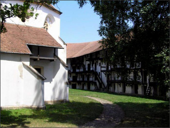 """Němci v Rumunsku postavili nejen sedm hradů za lesem (Sedmihradsko = Transylvánie tzn. trans sylva, za lesem). Obydleli celou část východního Rumunska a postavili zde sídla. Aby se ubránili Turkům organizovali středověkou domobranu. Své kostely obehnali zdí, se střílnami a zásobárnami. Když civilizace """"objevila"""" kostel v Prejmeru v roce 1950, visely ve spižírnách kusy špeku staré 200 let. Civilizovaná britská spisovatelka se zhrozila, ale správce kostela jí s úsměvem oznámil, že to je dobře: 200 let jsme zásoby nepotřebovali, nikdo nás neohrožoval!"""
