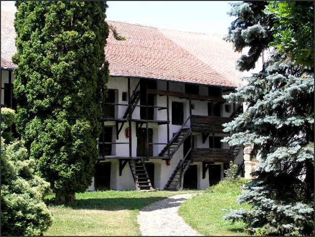 """Vlevo kostel, umístěný uprostřed hradeb; vpravo vnitřní část hradeb s """"bytečky"""" pro každou rodinu z vesnice."""
