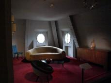 """Pohovku Boule (v češtině totéž) navrhl v roce 1947 Jean Royère pro byt své matky. Časem získala přezdívku """"Banane"""" (v češtině totéž) a rozšířila se do všech snobských bytů Paříže, Francie, světa. stejně jako křeslo Œuf (Vejce) v popředí a slaměná komoda."""
