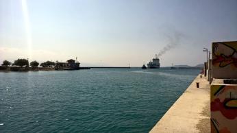 Uzoučké tankery a kontejnerové lodě, které jsou vyrobené pro Korint, čekají na širém moři, přivázané na mrňavém naváděcím remorkéru...